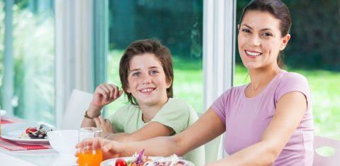 Mulher almoça salada e toma suco ao lado de seu filho