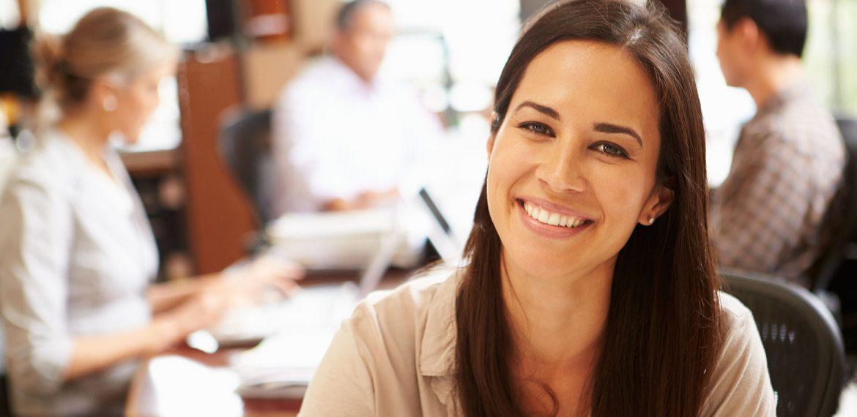 Funcionária sorridente se sente satisfeita com qualidade de vida no trabalho
