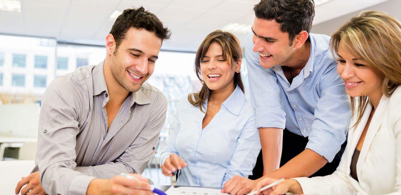 Equipe com quatro funcionários trabalha motivada para criar novo projeto.