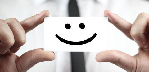 Pessoa segura com as mãos um papel com desenho de um sorriso