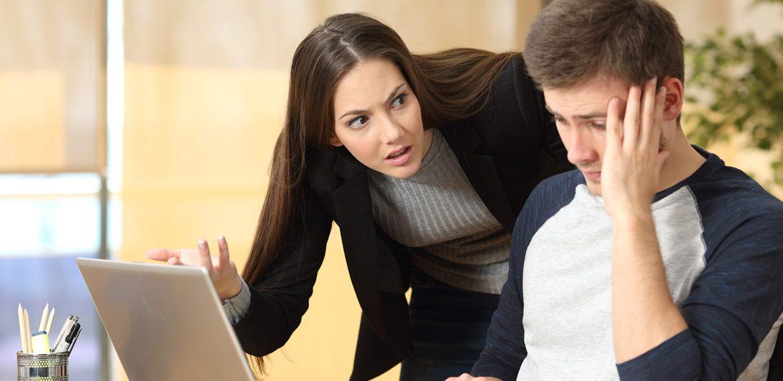 Mulher jovem nervosa faz pergunta a um funcionário homem que está sentado em frente ao seu notebook