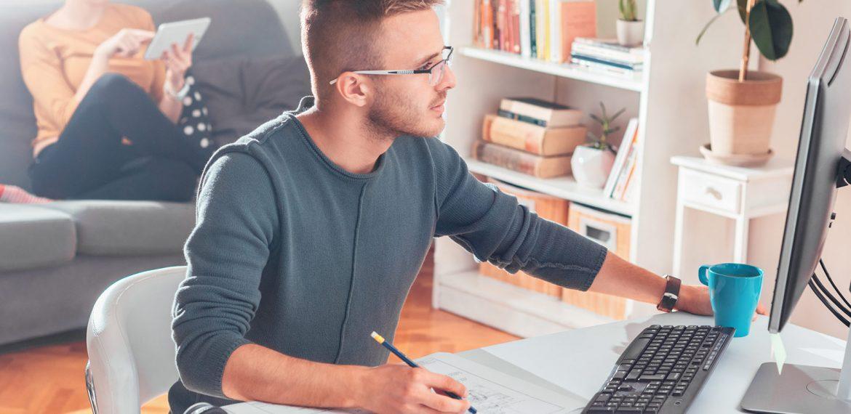 Homem jovem trabalha home office pelo computador