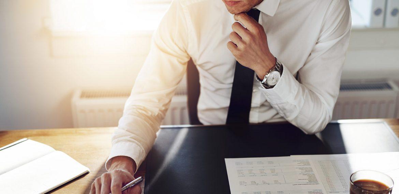 Homem executivo sentado em seu escritório e lendo relatórios