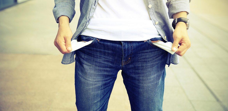 Homem tira seus bolsos da calça representando que está sem dinheiro