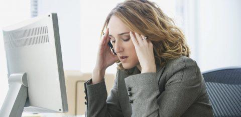 Mulher estressada em frente ao seu computador no trabalho