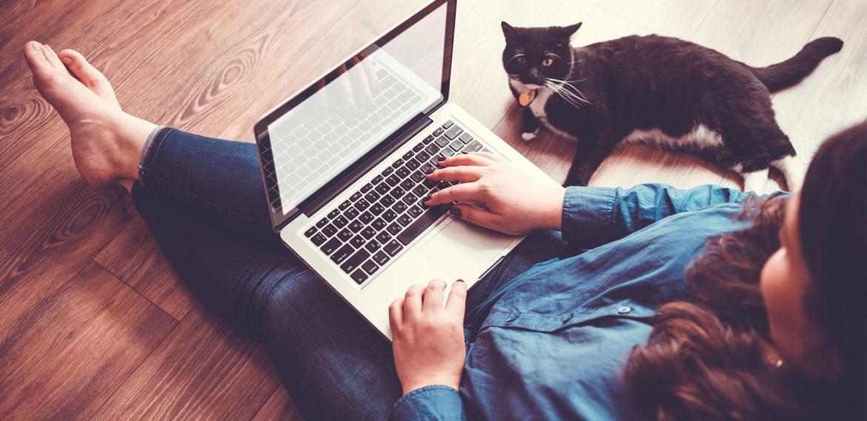 Mulher jovem sentada no chão com notebook no colo e gato ao lado