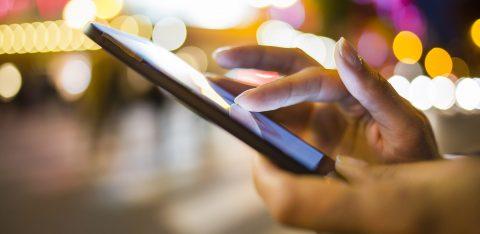 Pessoa mexendo em aplicativo em smartphone à noite