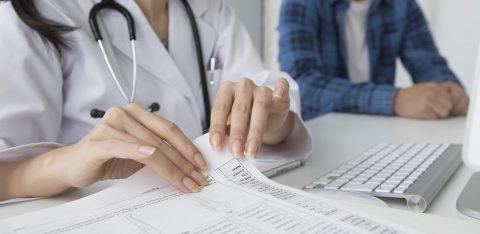 Médica checa papéis de paciente com plano de saúde