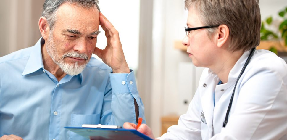 Médica escuta senhor que conta os sintomas que está tendo