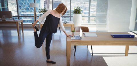 Mulher alonga a perna enquanto trabalha dentro do escritório