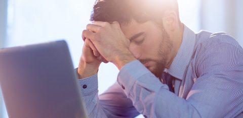 Homem cansado e estressado sentado em frente ao seu notebook