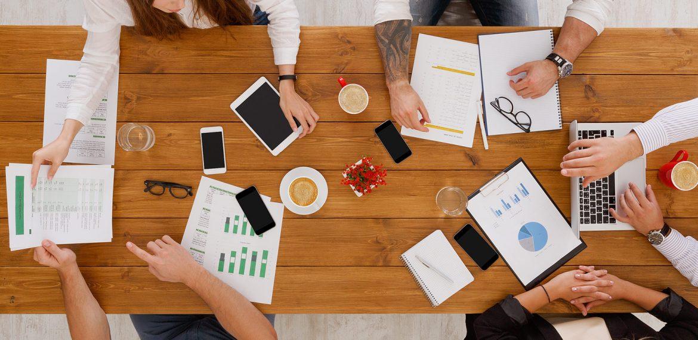 Equipe trabalha em conjunto em uma agência para analisar dados e propor plano de marketing para empresa