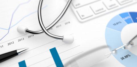 Estetoscópio e caneta em cima de folha com estatísticas