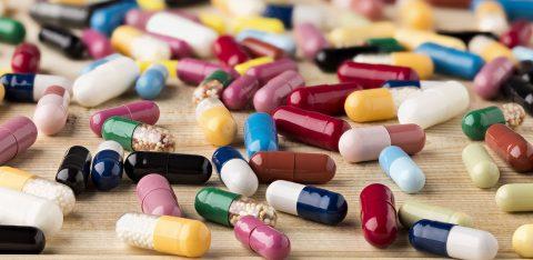 Comprimidos de medicamentos espalhados em cima de madeira