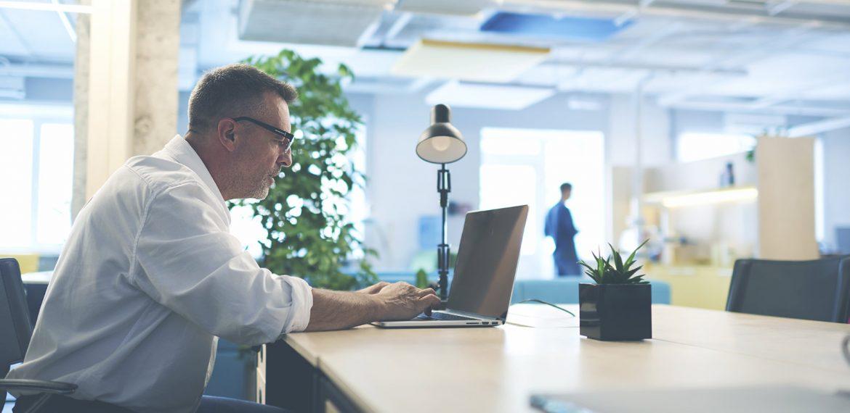 Homem trabalhando com um notebook em um escritório