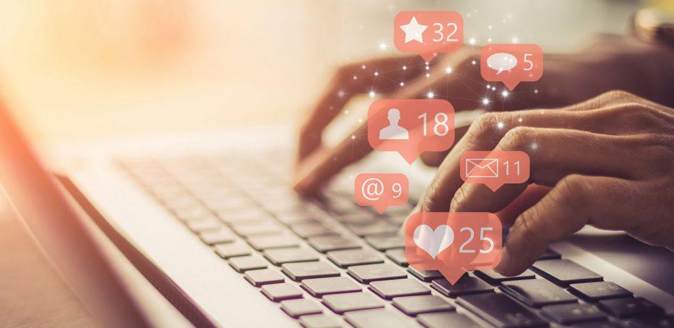 Pessoa digitando em teclado e sinais que representam curtidas, seguidores, compartilhamentos e engajamento do marketing digital