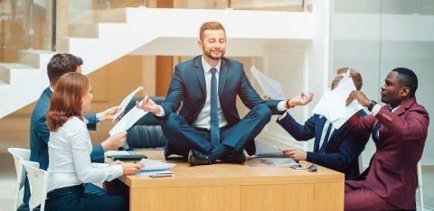 Homem executivo sentado em cima de mesa meditando ao lado de quatro funcionários que o chamam