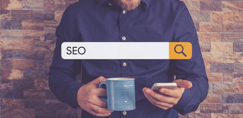 """Homem com celular e caneca azul nas mãos e tela de busca com a palavra """"SEO"""""""