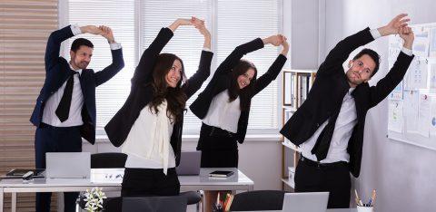 Quatro funcionários de empresa fazem alongamento no ambiente de trabalho