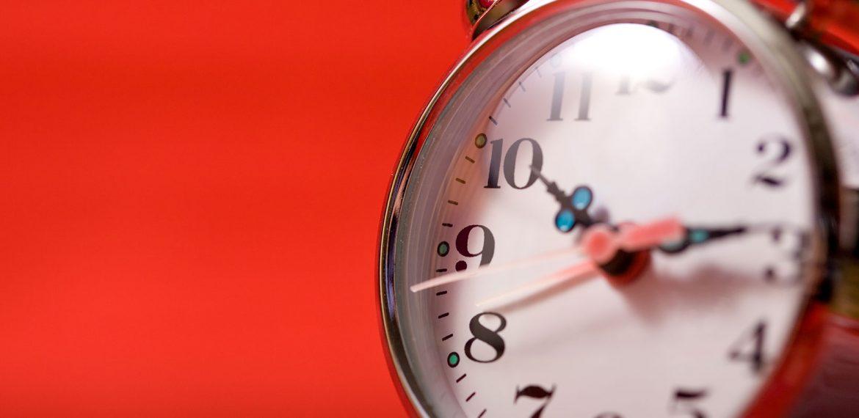Relógio de mesa com parede vermelha ao fundo