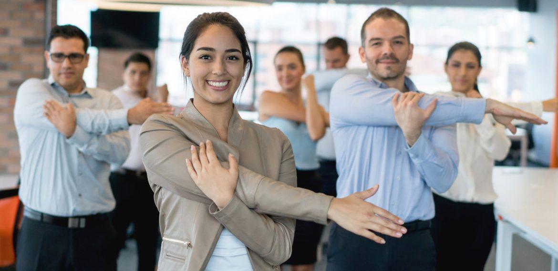 Funcionários se alongam no ambiente de trabalho em campanha de saúde de empresa