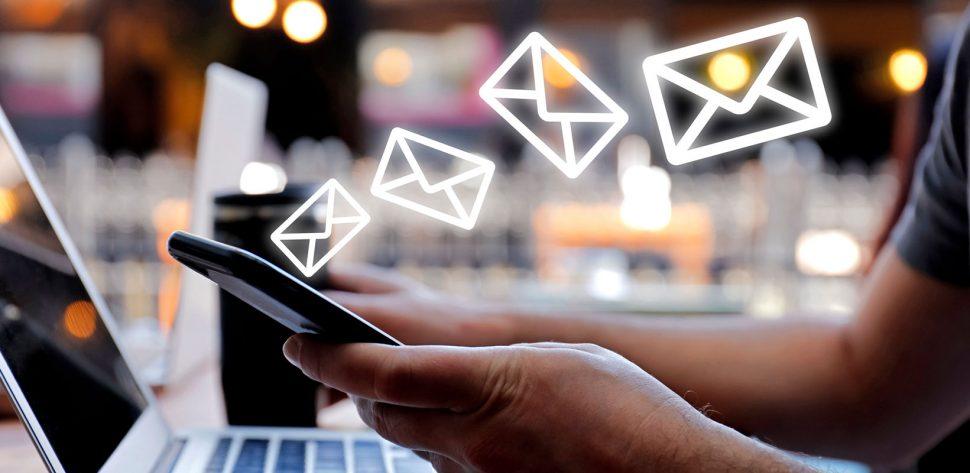 Indivíduo conectado com celular e notebook enquanto recebe vários e-mails