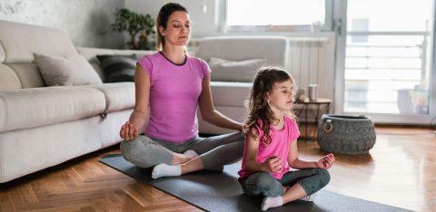 Mãe e filha meditando em casa