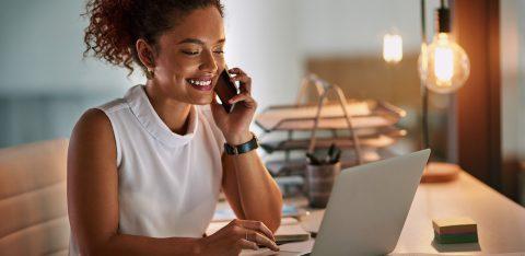 Mulher sorrindo ao telefone e utilizando um computador